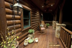 Log Home By Golden Eagle Log and Timber Homes - front porch   at night